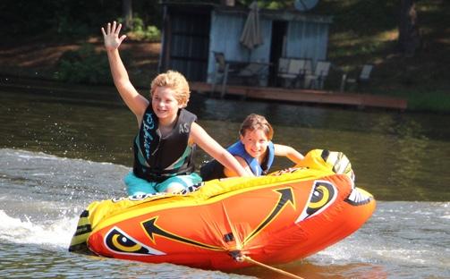 Boy and girl tubing on lake