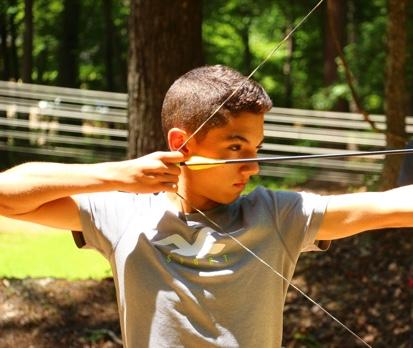 Boy shooting bow and arrow